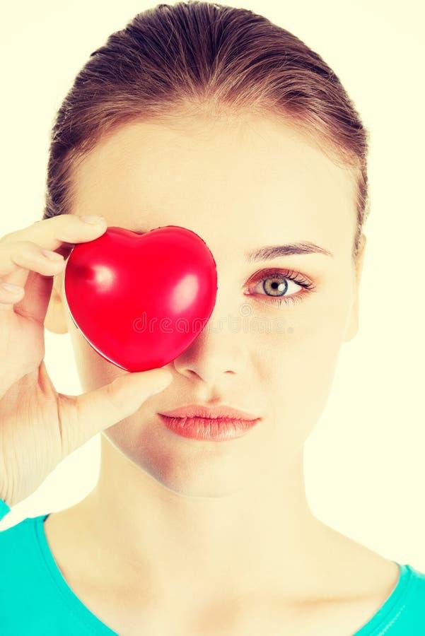 Hübsches Mädchen, das rotes Herz zeigt stockfotografie