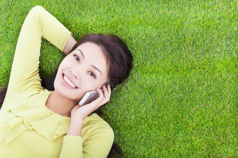 Hübsches Mädchen, das telefonisch in einer Wiese spricht lizenzfreie stockbilder