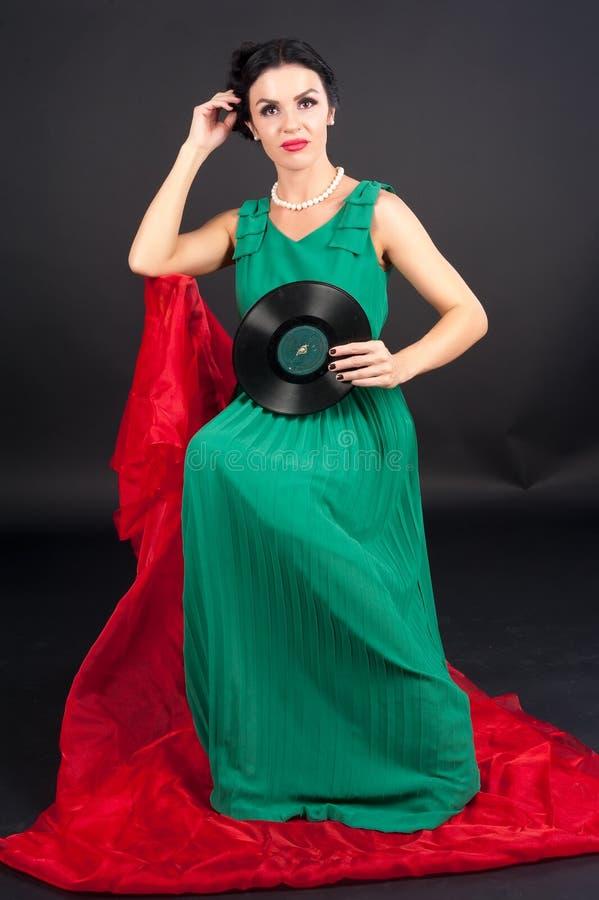 Hübsches Mädchen, das Vinylplatte anhält lizenzfreie stockbilder