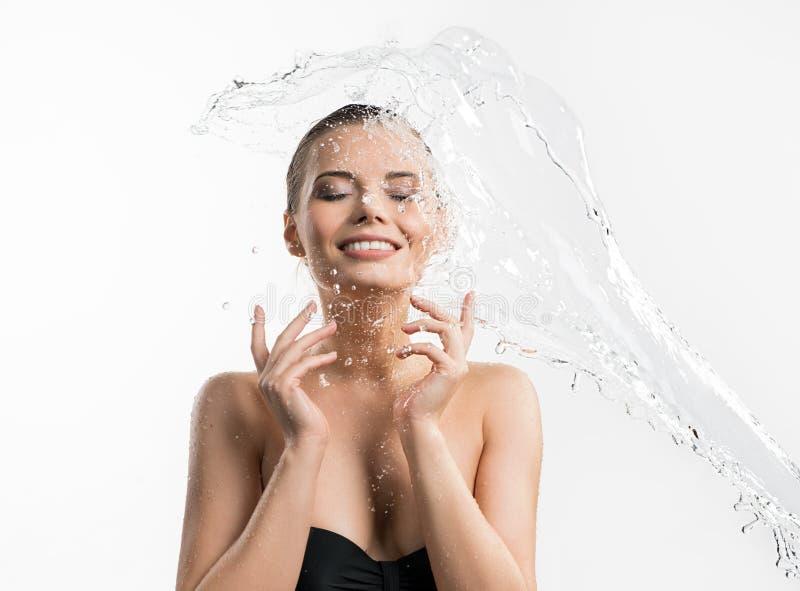 Hübsches Mädchen, das Wasserspritzenatelieraufnahme genießt lizenzfreie stockfotografie