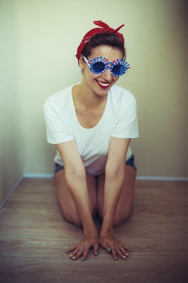 Hübsches Mädchen in der lustigen Sonnenbrille, gekleidet in einer Stift-obenart lizenzfreies stockfoto
