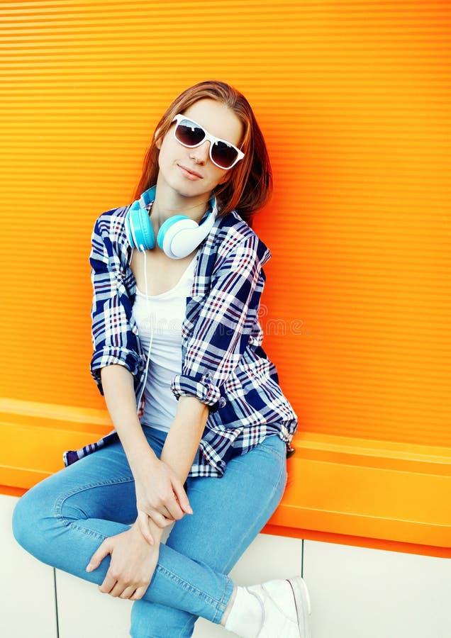 Hübsches Mädchen in der Sonnenbrille und in den Kopfhörern lizenzfreies stockfoto
