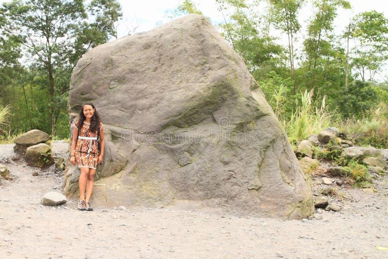 Hübsches Mädchen durch ausländischen Stein am Standpunkt zum Vulkan Merapi lizenzfreies stockbild