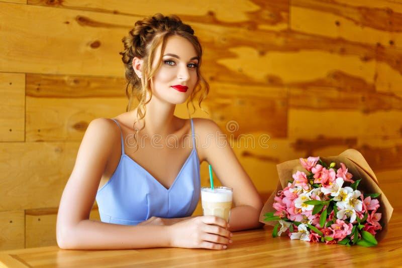 Hübsches Mädchen in einem blauen Kleid mit einem Blumenstrauß von den Blumen, die in einem Kaffeehaus sitzen lizenzfreie stockfotos