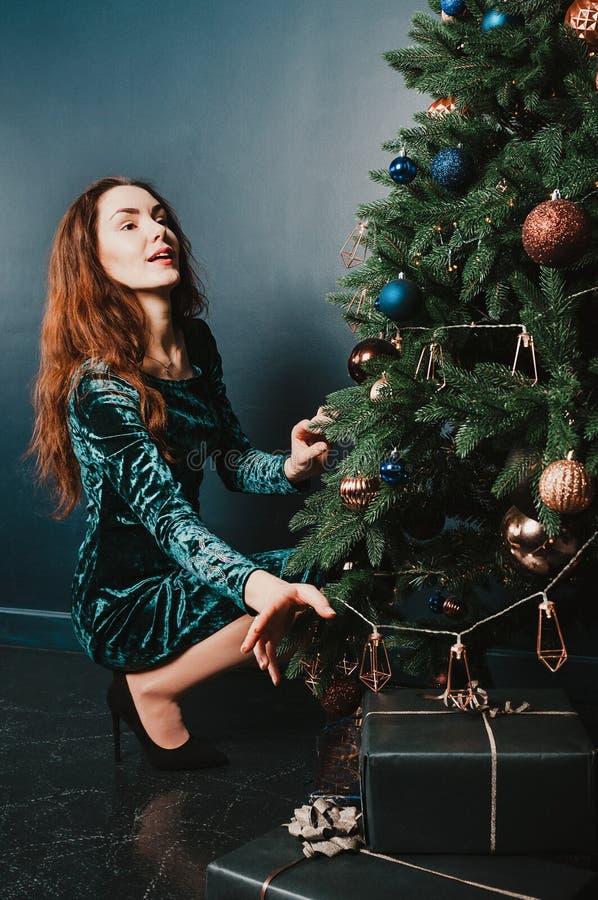 Hübsches Mädchen in einem Kleid mit Geschenkboxen nahe dem Weihnachtsbaum, oben schauend mit einem Lächeln Konzept des neuen Jahr stockfoto