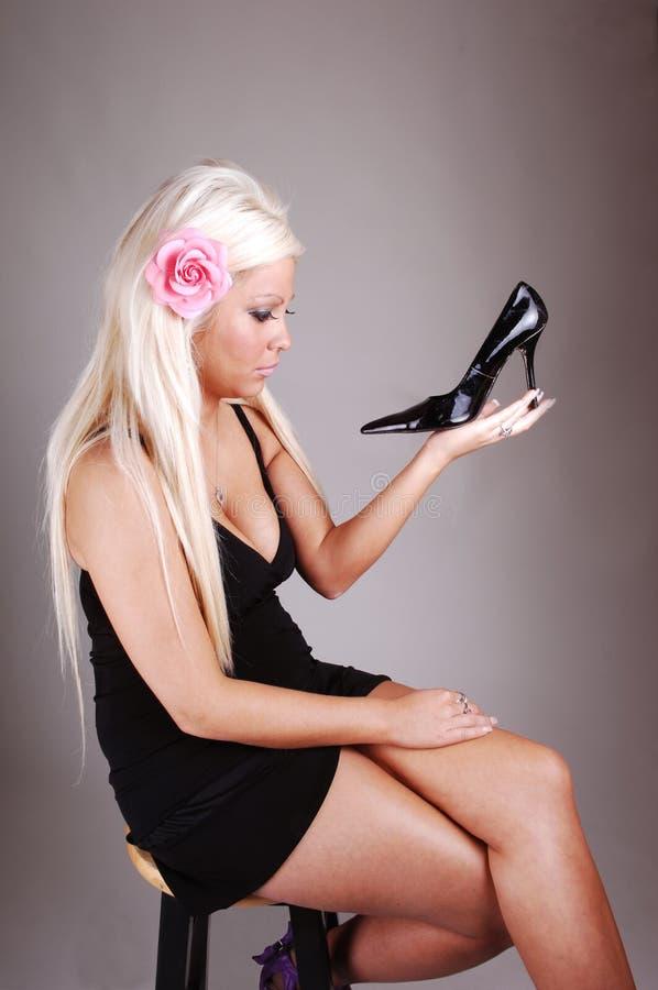 Hübsches Mädchen in einer schwarzen Kleidholding ihr Schuh. stockbild