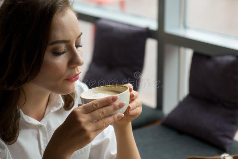 Hübsches Mädchen genießt einen wohlriechenden Kaffee und einen süßen Kuchen, die im Kaffeehaus sitzen Geschäftsfrau, die während  lizenzfreie stockfotografie