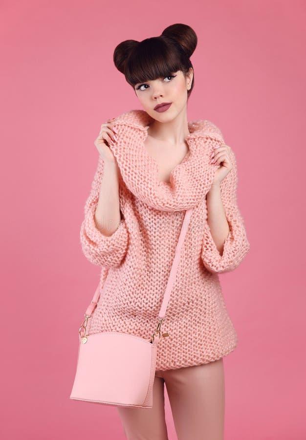 Hübsches Mädchen in gestrickter Strickjacke mit zufälliger Handtasche über rosa BAC stockbilder