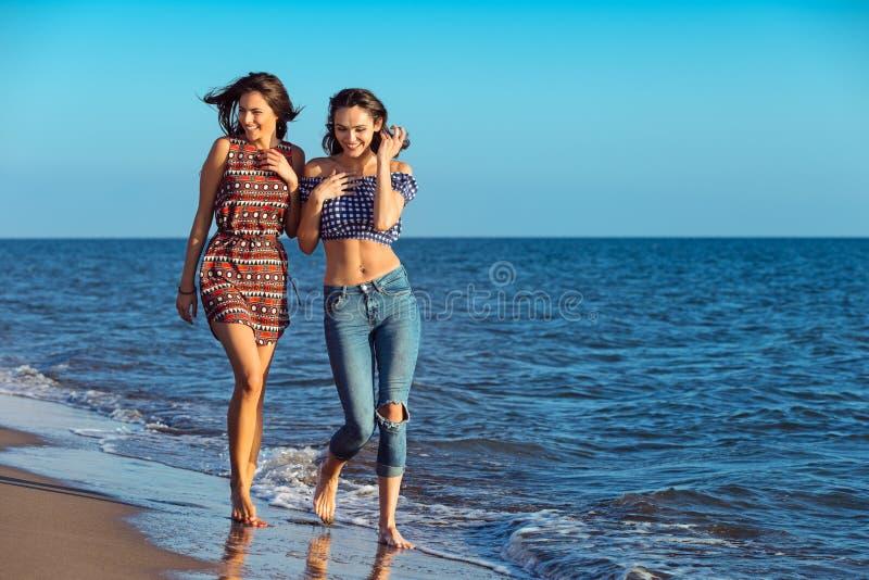 Hübsches Mädchen hat einen Spaß mit ihrer Freundin auf dem Strand stockbilder