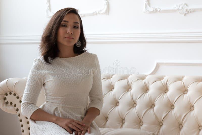 Hübsches Mädchen im weißen Kleid sitzt auf einer Ledercouch lizenzfreie stockbilder