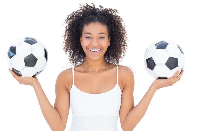 Hübsches Mädchen mit Afrofrisur lächelnd an der Kamera, die Fußball hält stockfotos