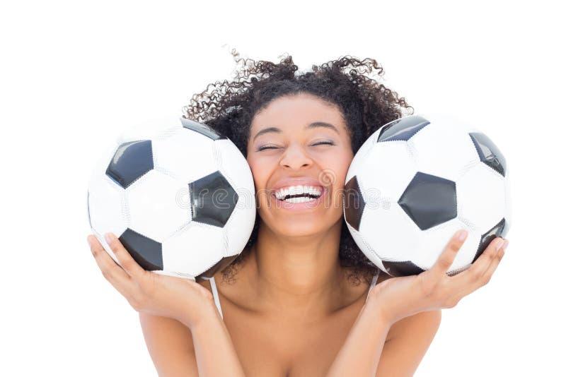 Hübsches Mädchen mit Afrofrisur lächelnd an der Kamera, die Fußball hält lizenzfreie stockfotografie