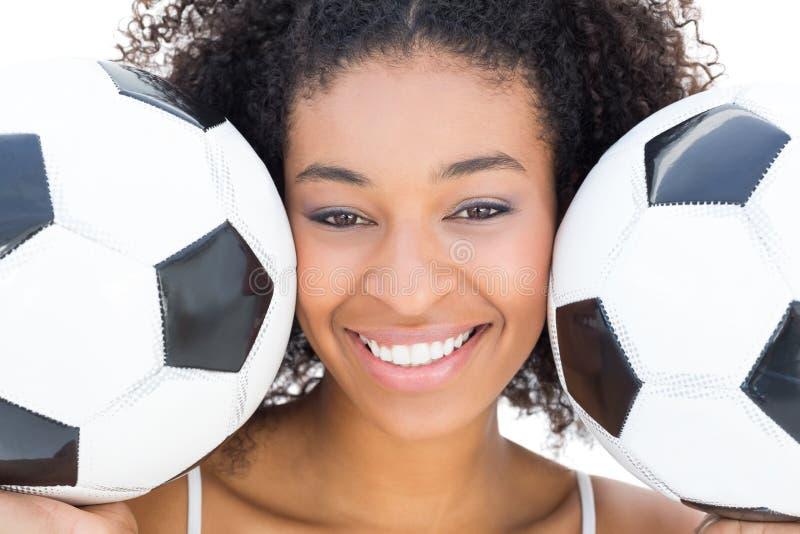 Hübsches Mädchen mit Afrofrisur lächelnd an der Kamera, die Fußball hält lizenzfreie stockfotos