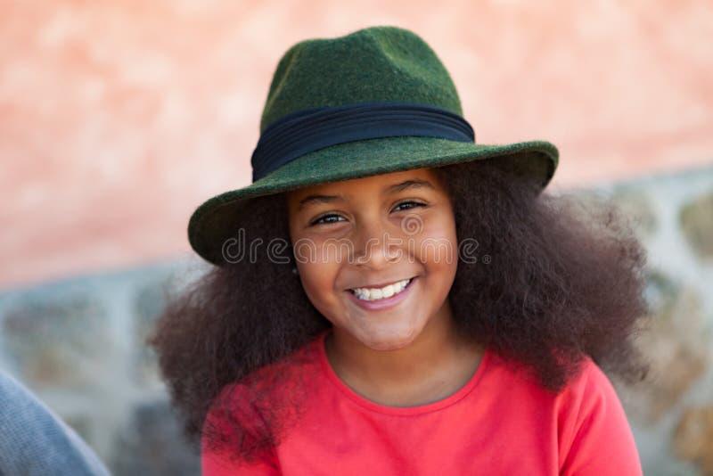 Hübsches Mädchen mit dem langen Afrohaar mit einem eleganten schwarzen Hut lizenzfreies stockbild