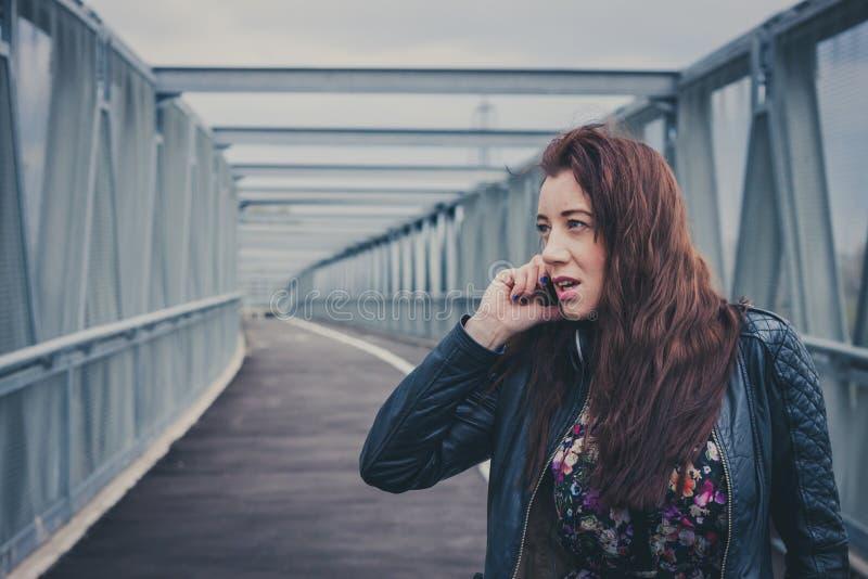 Hübsches Mädchen mit dem langen Haar sprechend am Telefon stockbild