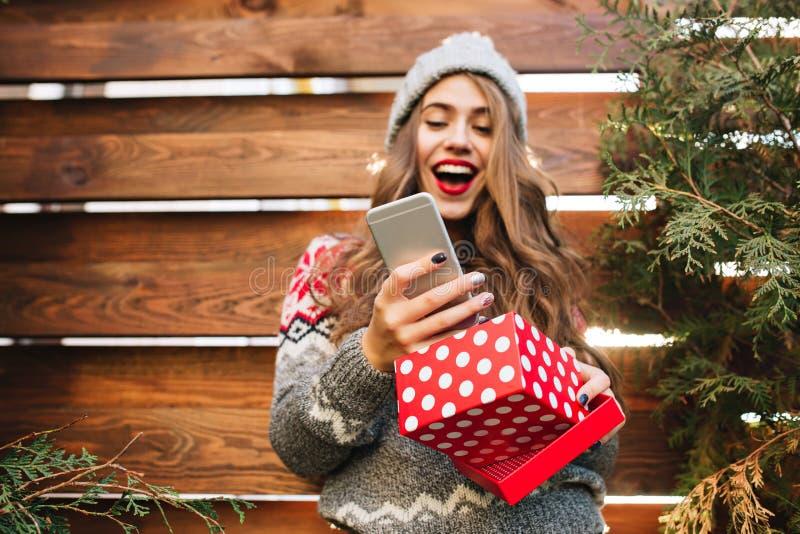 Hübsches Mädchen mit dem langen Haar mit Weihnachtskasten auf hölzernem Hintergrund Sie trägt warme Winterkleidung, Blicke erstau lizenzfreie stockbilder