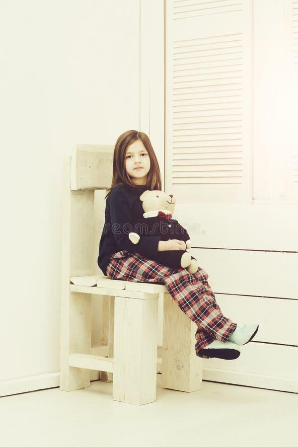 Hübsches Mädchen mit dem netten Teddybärspielzeug, das auf Stuhl sitzt lizenzfreie stockfotos