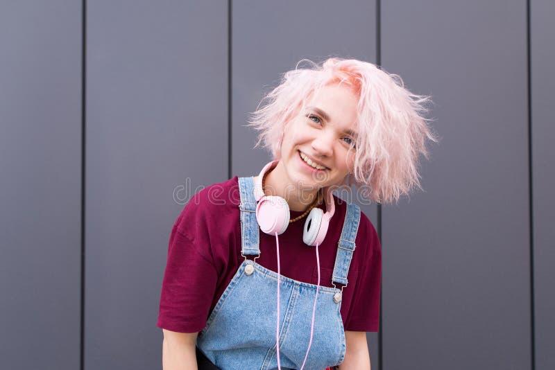 Hübsches Mädchen mit dem rosa Haar und den Kopfhörern lächelt echt am dunklen Hintergrund stockfoto