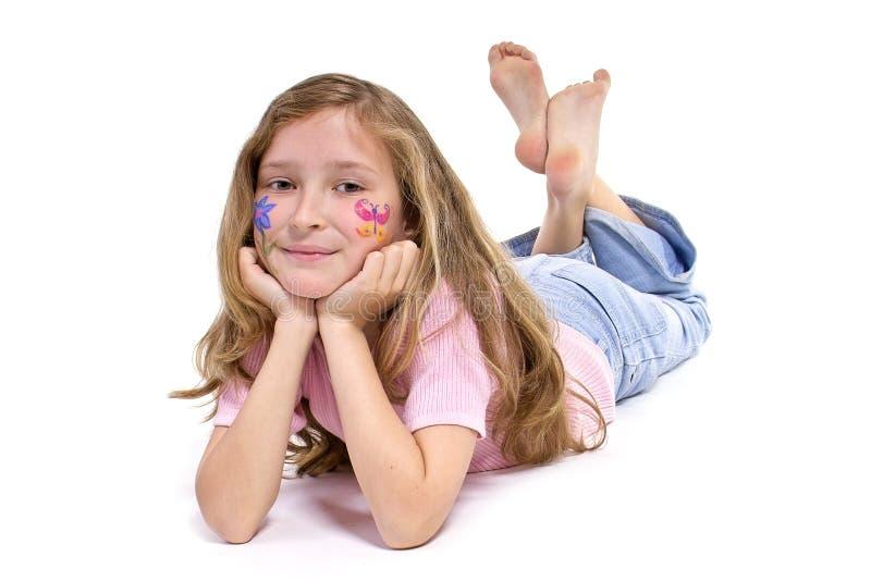 Hübsches Mädchen mit der Blumenbasisrecheneinheitsverfassung, die auf den Fußboden legt stockfoto