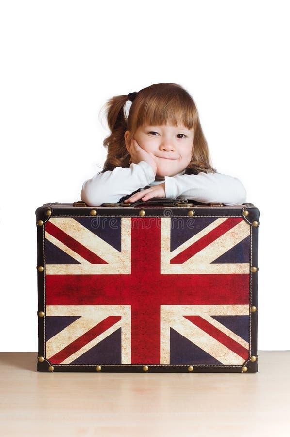 Hübsches Mädchen mit einem Koffer mit britischer Flagge stockbilder