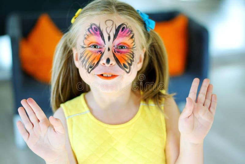 Hübsches Mädchen mit Gesichtsmalerei eines Schmetterlinges im gelben Kleid lizenzfreie stockfotos