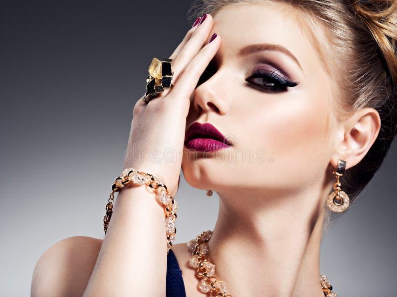 Hübsches Mädchen mit hellem Make-up des schönen Gesichtes und Goldschmuck lizenzfreies stockbild