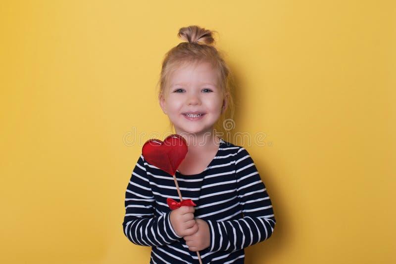 Hübsches Mädchen mit roter heller Lutschersüßigkeit auf gelbem Hintergrund lizenzfreies stockfoto