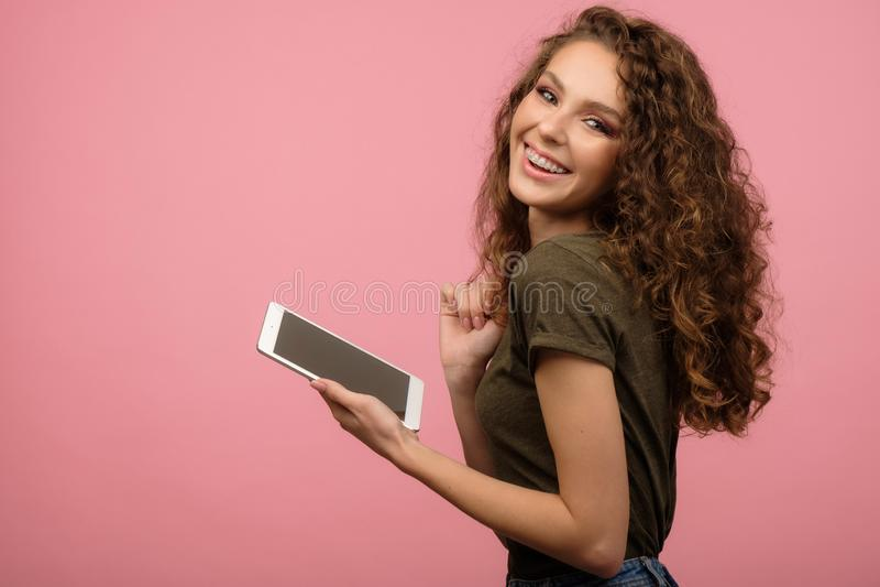 Hübsches Mädchen mit Tablette auf rosa Untergrund stockfoto