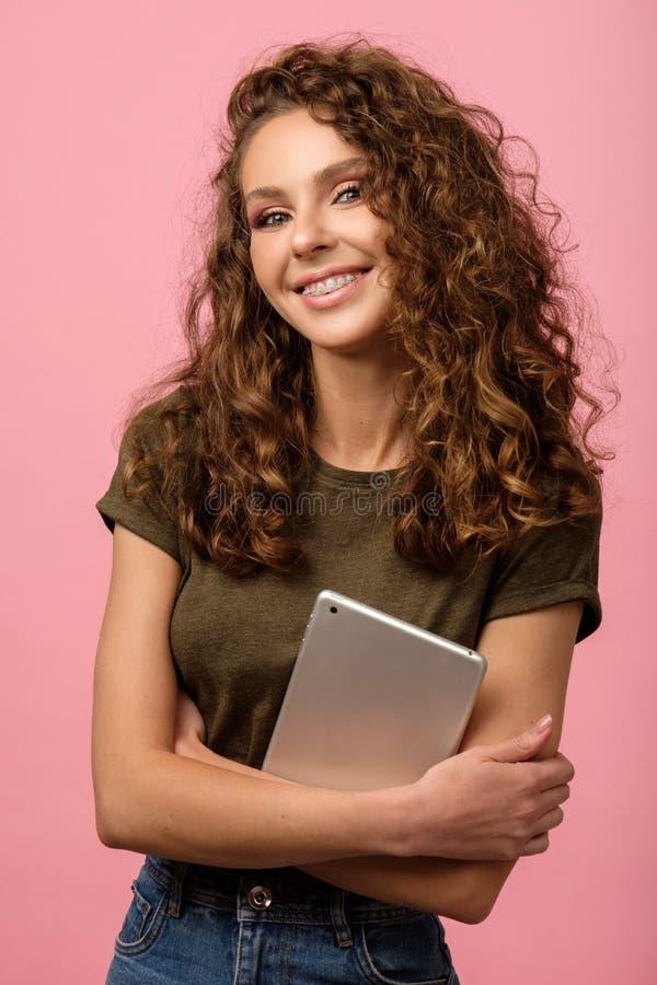 Hübsches Mädchen mit Tablette auf rosa Untergrund lizenzfreie stockbilder