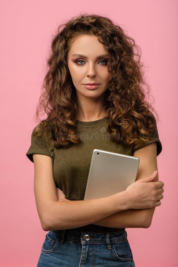 Hübsches Mädchen mit Tablette auf rosa Untergrund lizenzfreies stockbild