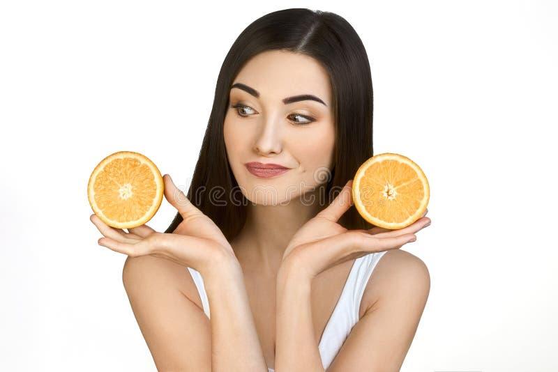 Hübsches Mädchen mit zwei Hälften der Orange in den Händen auf weißem Hintergrund lizenzfreies stockbild