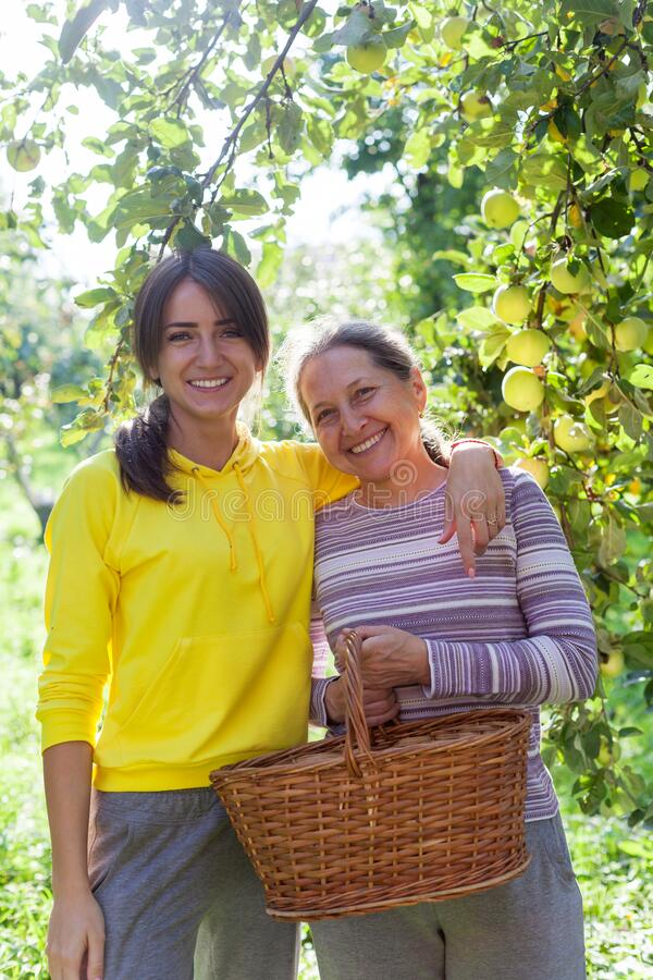 Hübsches Mädchen neben reifer Mutter im Garten lizenzfreies stockbild