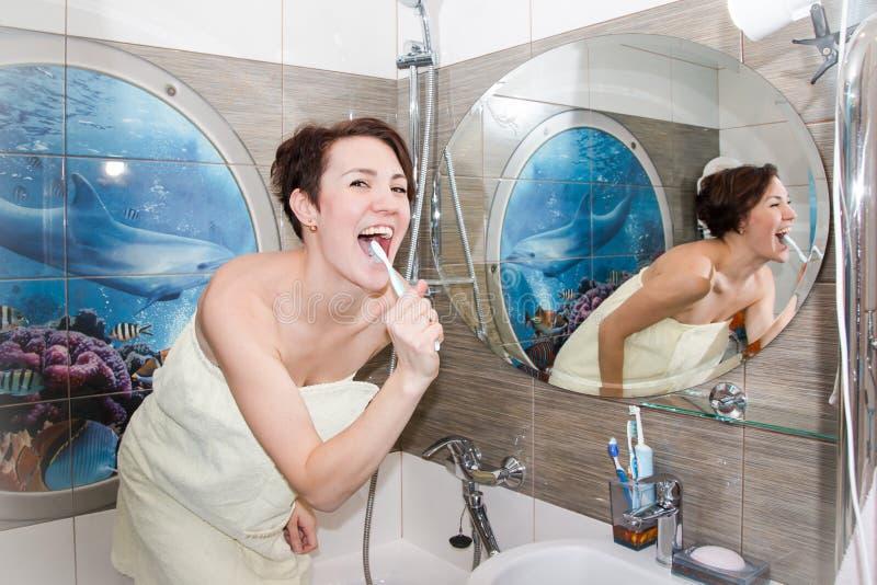 Hübsches Mädchen säubert Zähne in einem Badezimmer stockbild