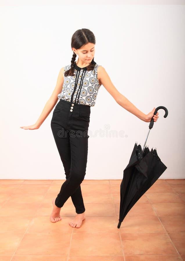 Hübsches Mädchen in Schulbekleidung mit schwarzem Schirm stockfotos