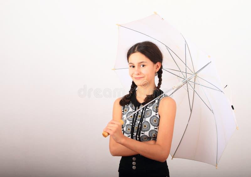 Hübsches Mädchen in Schulbekleidung mit weißem Schirm lizenzfreies stockfoto
