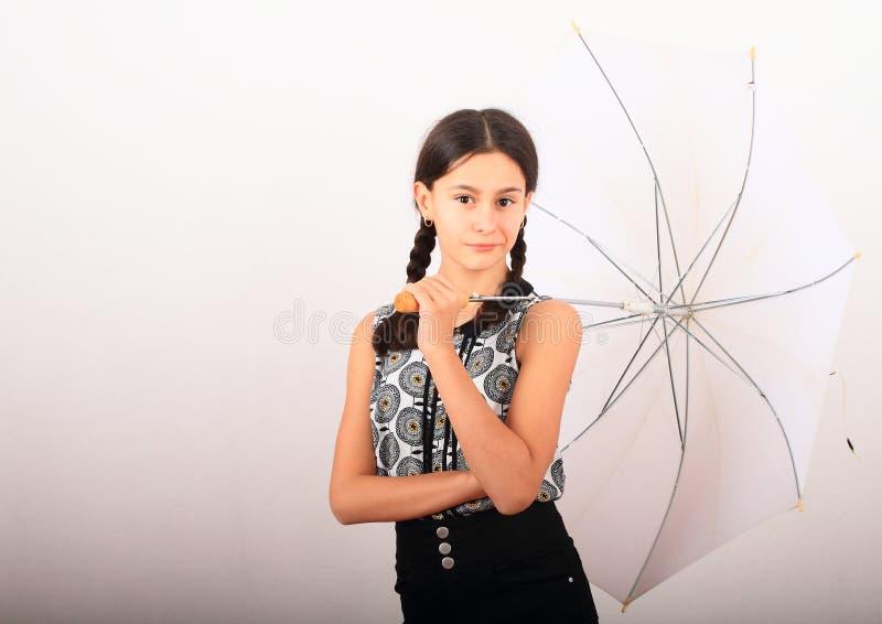 Hübsches Mädchen in Schulbekleidung mit weißem Schirm stockfotografie