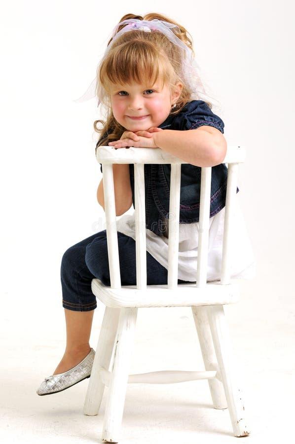 Hübsches Mädchen in sitzendem weißem Stuhl des blauen Kleides stockfotografie