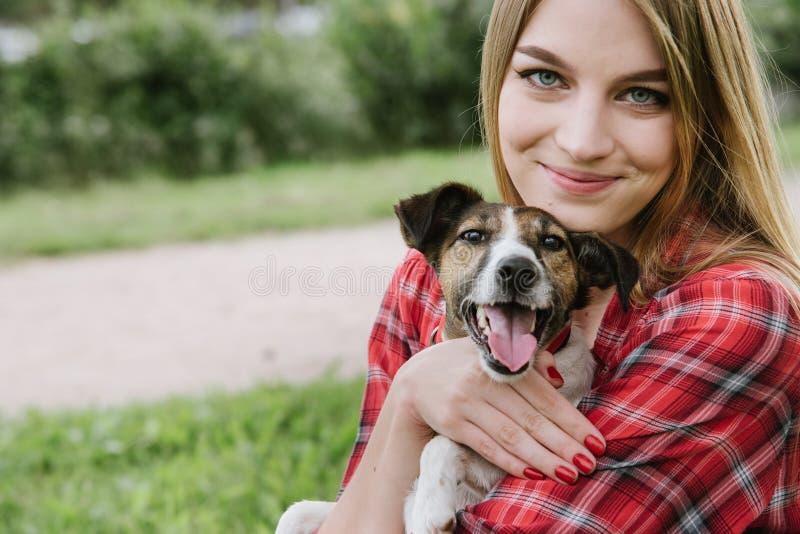 Hübsches Mädchen umfassen ihren Hund lizenzfreie stockfotos
