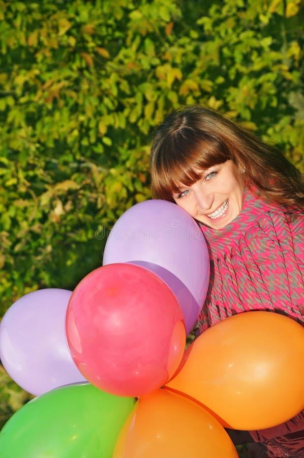 Hübsches Mädchen und bunte Ballone lizenzfreie stockfotos