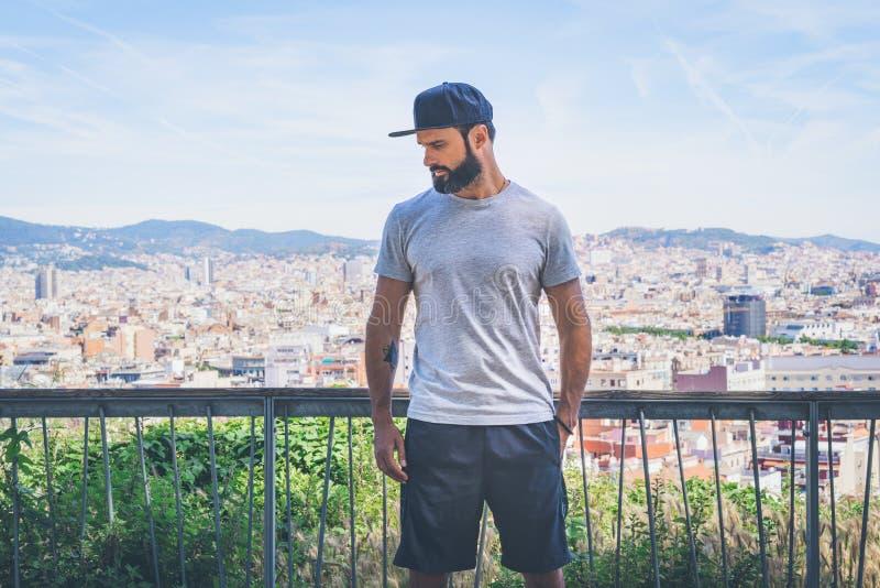 Hübsches männliches Modell des Hippies mit dem Bart, der graues leeres T-Shirt und eine schwarze Hysteresenkappe mit Raum für Ihr stockbild