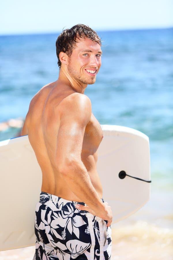 Hübsches männliches Surferporträt auf Sommerstrand stockfotografie