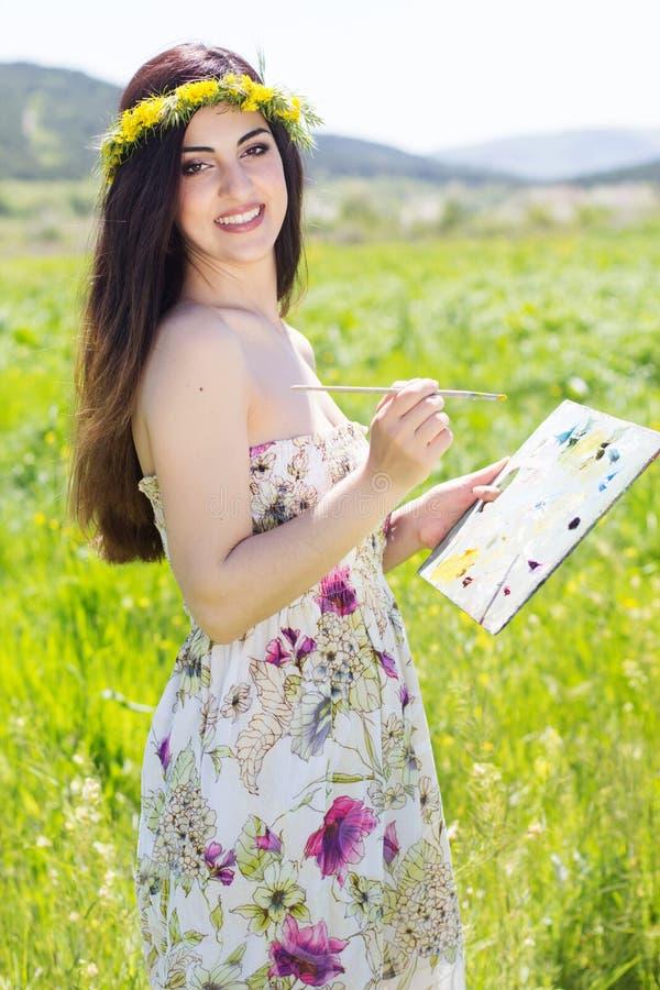 Hübsches Malermädchen mit Palette auf dem Gebiet lizenzfreies stockbild