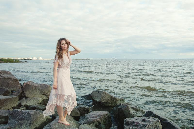 Hübsches Modell im beige Kleid auf romantischem Porträt der Ozeanküste der schönen jungen Frau stockfoto