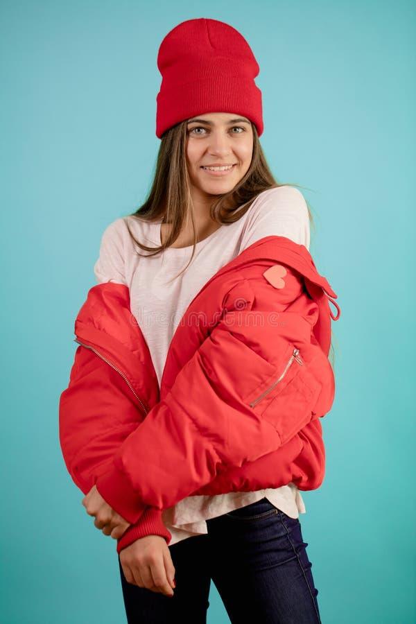 Hübsches Modell trägt Rot unten-aufgefüllten Mantel und gelesene Kappe bereiten Sie zum Winter vor lizenzfreies stockfoto