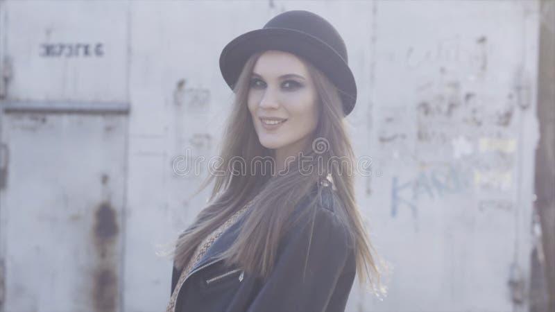 Hübsches modisches Mädchen mit schwarzem stilvollen Hut und der Lederjacke, die am Altbau im warmen Sonnenlicht aufwirft t?tigkei stockfotos