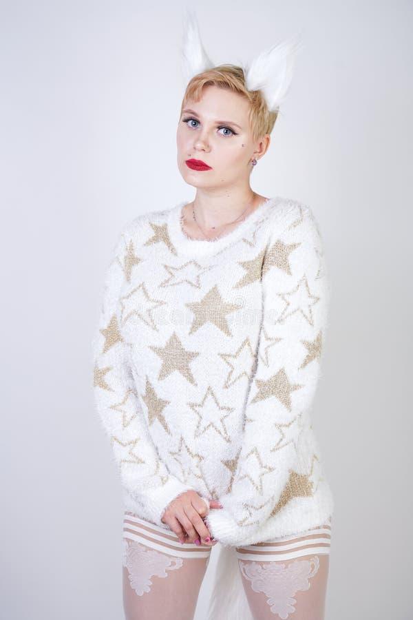 Hübsches nettes nettes Mädchen mit dem blonden kurzen Haar und tragender weißer Strickjacke des curvy Plusgrößenkörpers mit golde stockbild