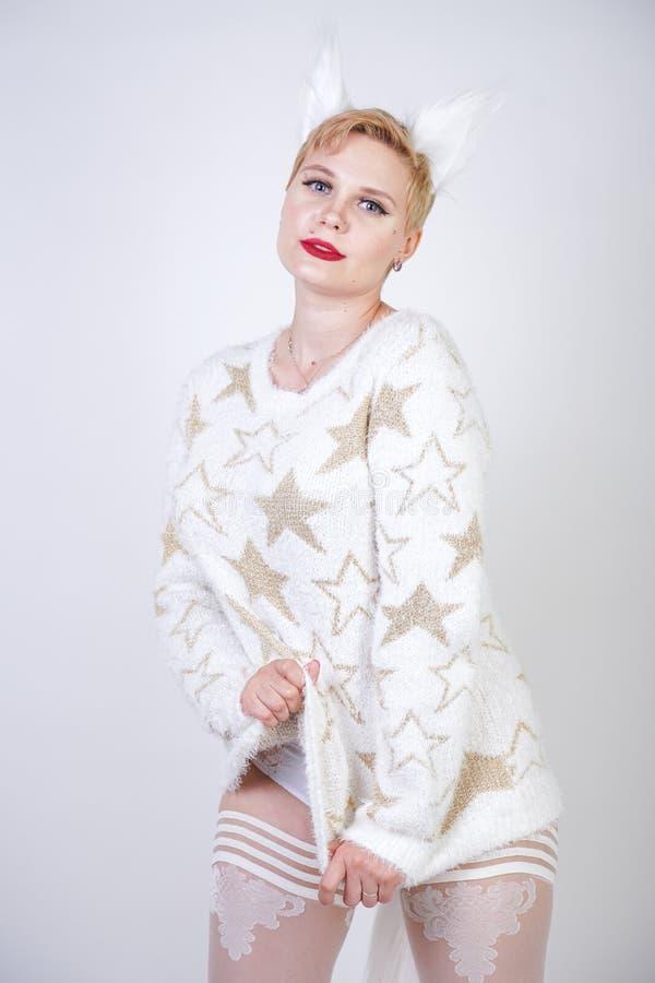 Hübsches nettes nettes Mädchen mit dem blonden kurzen Haar und tragender weißer Strickjacke des curvy Plusgrößenkörpers mit golde lizenzfreie stockfotos