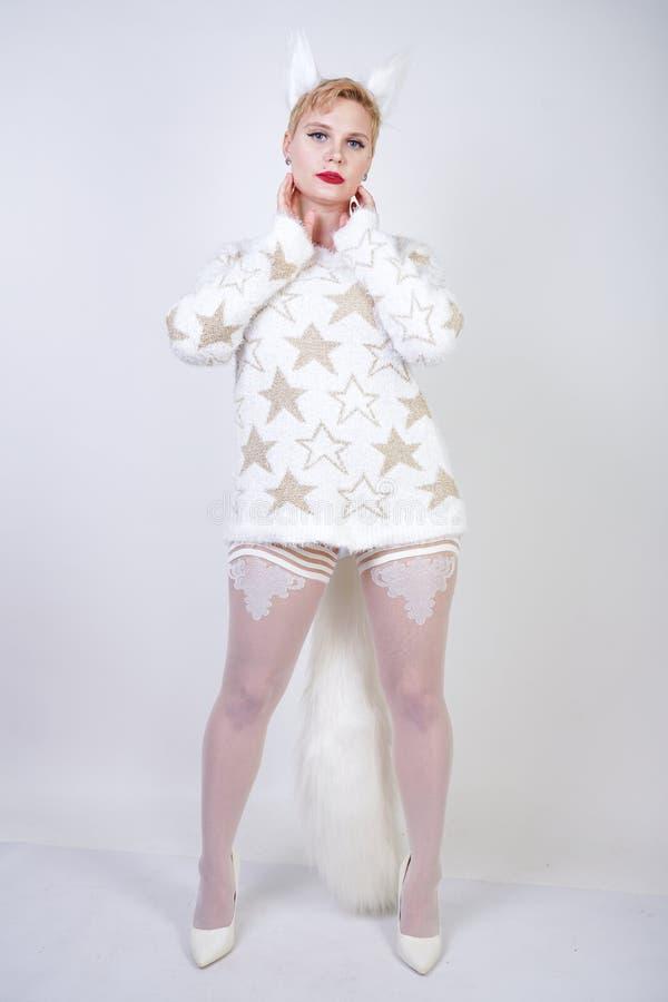 Hübsches nettes nettes Mädchen mit dem blonden kurzen Haar und tragender weißer Strickjacke des curvy Plusgrößenkörpers mit golde stockbilder