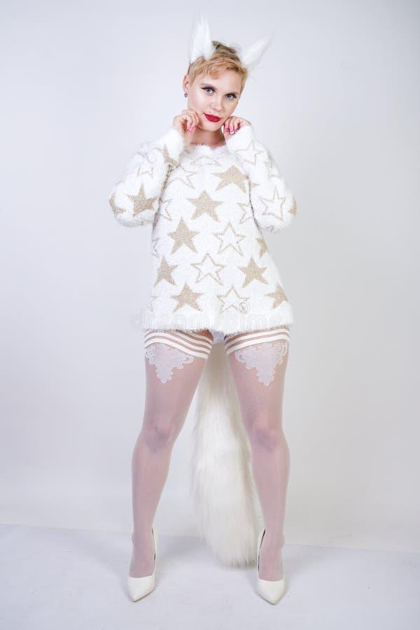 Hübsches nettes nettes Mädchen mit dem blonden kurzen Haar und tragender weißer Strickjacke des curvy Plusgrößenkörpers mit golde stockfoto