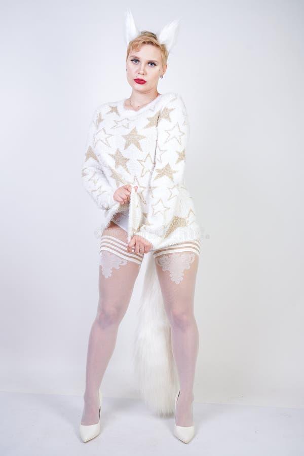 Hübsches nettes nettes Mädchen mit dem blonden kurzen Haar und tragender weißer Strickjacke des curvy Plusgrößenkörpers mit golde stockfotografie